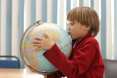 Um menino que beija um mapa do globo na classe da geografia e que aprende imagem de stock royalty free