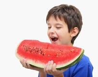 Um menino que come a melancia Imagem de Stock