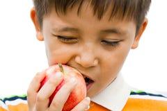 Um menino que come uma maçã fotos de stock royalty free