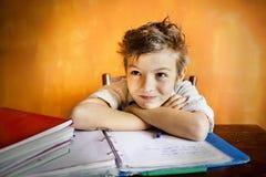 Um menino que concentra-se em trabalhos de casa Imagens de Stock Royalty Free