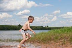 Um menino que corre fora do rio Foto de Stock