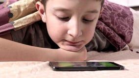Um menino que encontra-se em uma cama em casa, relaxando e olhando o vídeo no smartphone vídeos de arquivo