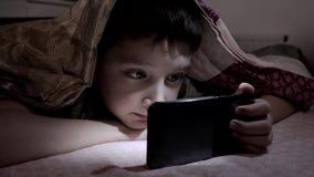Um menino que encontra-se em uma cama em casa, relaxando e olhando o vídeo no smartphone na obscuridade sob a cobertura vídeos de arquivo