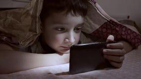 Um menino que encontra-se em uma cama em casa, relaxando, sorrindo e olhando o vídeo no smartphone na obscuridade sob a cobertura vídeos de arquivo
