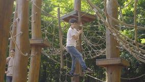 Um menino que escala em um equipamento do campo de jogos video estoque