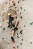 Um menino que escala em uma parede da rocha. Foto de Stock
