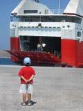 Um menino que espera o barco Imagens de Stock Royalty Free