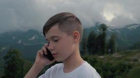 Um menino que fala em um smartphone ao viajar contra o contexto das montanhas altas video estoque