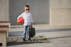 Um menino que guarda um moneybox e uma mala de viagem vermelhos foto de stock