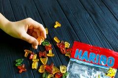Um menino que guarda o bloco da geleia de Haribo na tabela escura Haribo é uma empresa alemão dos confeitos imagem de stock