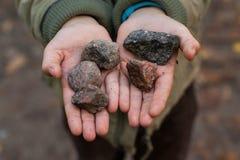 Um menino que guarda pedras em suas mãos fotos de stock royalty free