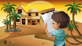 Um menino que guarda um papel vazio no deserto Foto de Stock Royalty Free