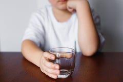 Um menino que guarda um vidro vazio e esperas Fotos de Stock