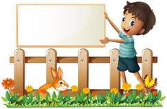 Um menino que guardara uma placa quadro no jardim Fotografia de Stock