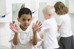Um menino que indica suas mãos em um banheiro da escola Imagens de Stock Royalty Free