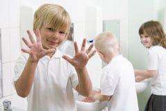 Um menino que indica suas mãos em um banheiro da escola Imagem de Stock