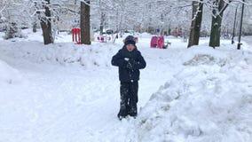 Um menino que joga bolas de neve no parque nevado do inverno - conceito da infância, do lazer e da estação filme