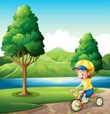 Um menino que joga com sua bicicleta pequena Imagens de Stock Royalty Free