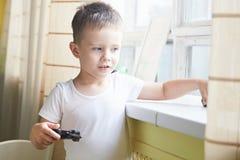 Um menino que joga com um telecontrole do carro Fotografia de Stock
