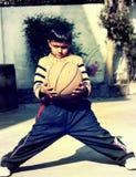 Um menino que joga o basquetebol Fotografia de Stock