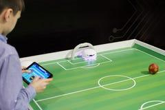 Um menino que joga o futebol da tabela com uma bola vermelha com um robô em um g Imagens de Stock