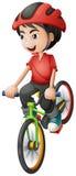 Um menino que monta sua bicicleta Fotografia de Stock Royalty Free