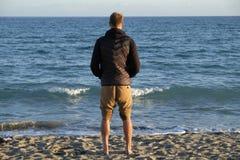Um menino que olha o panorama sobre o horizonte de mar na praia - estação do inverno no por do sol fotos de stock royalty free