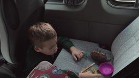 Um menino que senta-se em um assoalho dos carros que joga com alguns brinquedos em um banco traseiro vídeos de arquivo