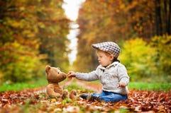Um menino que senta-se em uma estrada de floresta fotos de stock royalty free