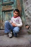 Um menino que senta-se na entrada Imagem de Stock