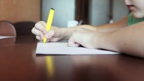 Um menino que senta-se na mesa e em esboços de pintura com o marcador colorido no Livro Branco video estoque