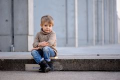 Um menino que senta-se nas etapas imagem de stock royalty free