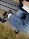 Um menino que senta-se no banco Imagem de Stock