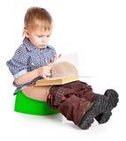 Um menino que senta-se no potenciômetro Imagens de Stock Royalty Free