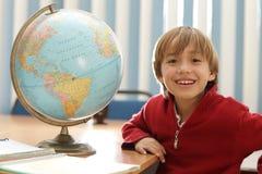 Um menino que sorri além de um mapa do globo na classe da geografia e que aprende Fotografia de Stock