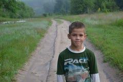 Um menino que sorri nas madeiras Imagem de Stock Royalty Free