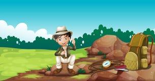 Um menino que veste um chapéu que senta-se em uma rocha Foto de Stock