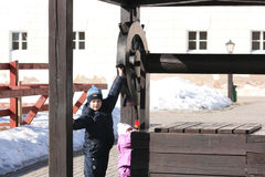 Um menino recolhe a água de um poço Imagens de Stock Royalty Free
