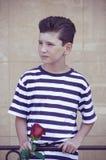 Um menino romântico novo com um penteado elegante e uma rosa Imagem de Stock