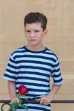Um menino romântico novo com um penteado elegante e uma rosa Imagens de Stock