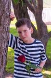 Um menino romântico novo com um penteado elegante e uma rosa Fotos de Stock Royalty Free