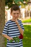 Um menino romântico novo com um penteado elegante e uma rosa Fotografia de Stock