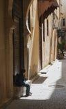 Um menino senta-se na frente da porta que espera seu pai após a parte traseira da escola Imagens de Stock Royalty Free