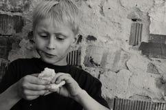 Um menino sujo com fome come avidamente uma crosta do pão contra a parede Rebecca 36 foto de stock royalty free