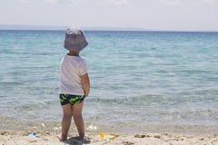 Um menino tímido pequeno com o chapéu que está na areia perto da água e do lo imagem de stock