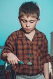 Um menino triste nos pijamas não é afiado escovar seus dentes antes de ir dormir em um fundo azul fotos de stock