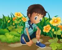 Um menino triste perto das flores de florescência Fotos de Stock