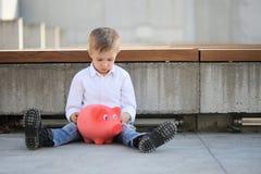 Um menino triste que guarda um moneybox e uma mala de viagem vermelhos fotos de stock royalty free
