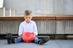 Um menino triste que guarda um moneybox e uma mala de viagem vermelhos fotografia de stock royalty free