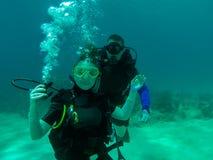 Um mergulho do mergulhador dos pares junto Um mergulhador de mergulhador fêmea com o regulador para fora Sorriso, guardando o reg Imagens de Stock
